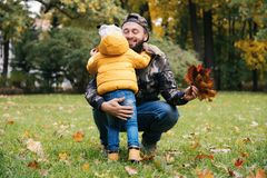 Happy father hugging his daughter outside. Family having fun in autumn park. Father`s day stock photography