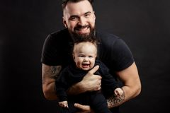 Young athletic father with adorable baby on black background. Happy father and infant daughter posing with different grimaces at studio black background witj stock photography