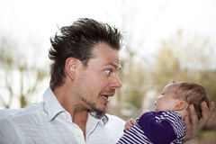 Happy father joking with baby girl. A happy father making faces and joking with his eight weeks old baby girl stock photos
