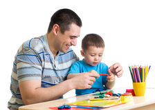 Happy father and kid boy play clay together. Happy father and child boy play clay together royalty free stock photos