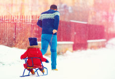 Happy father and kid having fun with sledge under winter snow Royalty Free Stock Photo