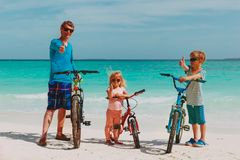 Happy father with kids biking on beach. Vacation stock photo