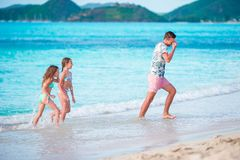 Happy father with kids play on beach. Happy family having fun during summer beach vacation. Father and kids enjoying beach summer vacation Stock Images