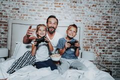 Happy father and kids playing with game console. Family relationship concept. Portrait of happy men with popcorn plate watching how his son and daughter playing stock images