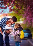 Happy father with kids on the walk in spring city, baby carrier, paternal leave. Happy father with cute kids on the walk in spring city, baby carrier, paternal Stock Image