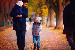 Father with kids walking along the autumn street Royalty Free Stock Photo