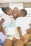 Happy father is kissed by his two children. In living room Royalty Free Stock Photos