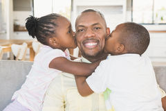 Happy father is kissed by his two children. In living room Stock Photos