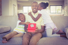Happy father is kissed by his two children. In living room Royalty Free Stock Image