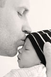 Happy father kisses newborn son Stock Photography