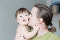 Happy father kissing baby daughter portrait. Happiness in simple lifestyle. Handsome bearded young man holding infant. Happy father kissing baby daughter Royalty Free Stock Photos