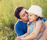 Happy father kissing her laughing daughter in hat on summer gree Stock Image