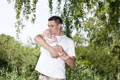 Happy father kissing his baby girl. A happy and proud young father kissing his 15 weeks old baby girl on her cheek Stock Photo