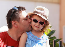 Happy father kissing his daughter. In fashion pink glasses Royalty Free Stock Image