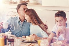 Happy father kissing his daughter into forehead. Tenderness in the air. Delighted girl sitting in semi position between her brother and dad, eating cake while Stock Images