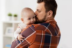 Happy father kissing little baby boy at home Stock Photo