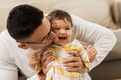 Happy father kissing little baby daughter at home. Family, fatherhood and people concept - happy father kissing his little baby daughter at home Stock Images