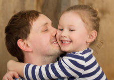 Happy father kissing little daughter Stock Photos