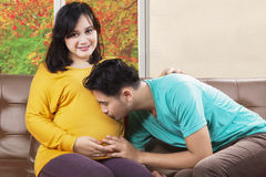 Happy father kissing pregnant belly. Portrait of happy father kissing pregnant belly of his wife while sitting on sofa with autumn background on the window Stock Photography