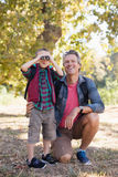 Happy father kneeling by boy looking through binoculars. Happy mature father kneeling by boy looking through binoculars in forest Royalty Free Stock Photo