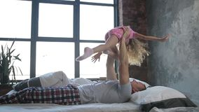 Happy father letting his daughter fly in bedroom stock video footage