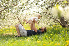 Happy Father lifting Baby Girl Playfully in Meadow Stock Photo