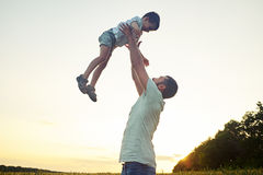 Happy father lifting his small son on background of sunset sky Royalty Free Stock Photo