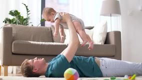 Happy father with little baby boy playing at home. Family, fatherhood and people concept - happy father with little baby boy lying on floor and playing at home stock footage