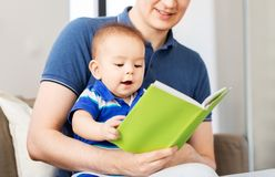 Happy father and little baby son with book at home royalty free stock photography