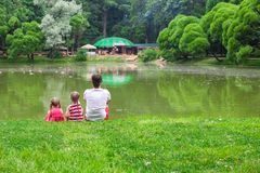 Happy father and little daughers relax by the lake Royalty Free Stock Photography