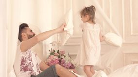 Happy father and little daughter having a pillow fight in bed stock video