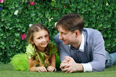 Happy father and little daughter lie on grass. Near hedge with flowers in garden stock images