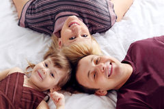 Happy father, little daughter and mother lie on bed Royalty Free Stock Photos