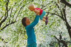 Happy father and little daughter play in spring nature, apple blossom stock photo