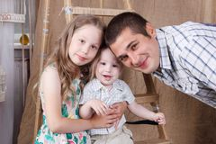 Happy father, little daughter and son smile and pose. On ladder in studio royalty free stock photo