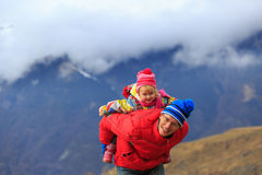Happy father and little daughter travel in winter mountains Royalty Free Stock Photo