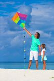 Happy father and little girl flying kite together Stock Image