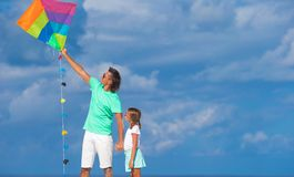 Happy father and little girl flying kite together Royalty Free Stock Photo