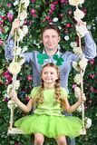 Happy father and little girl with shamrock on head on swing Royalty Free Stock Image