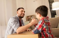 Happy father and little son arm wrestling at home stock images