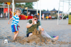 Happy father and and little son building sand castle on sand bea Stock Image