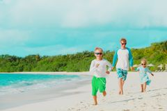 Happy father with little son and daughter walk at beach. Vacation stock image