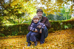 Happy father with little son having fun in autumn park. Stock Photos