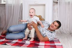Happy father with little son lie on floor. In room with decorative fireplace Stock Images