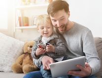 Happy father and little son with tablet at home royalty free stock image