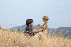 Happy father and little son rest in montains Royalty Free Stock Photos