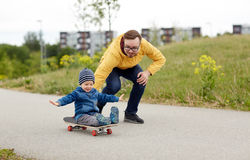 Happy father and little son riding on skateboard Stock Image