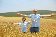 Happy father with little son walking happily in wheat field Royalty Free Stock Images
