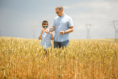 Happy father with little son walking happily in wheat field Royalty Free Stock Image