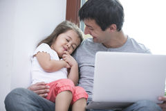 Happy father looking at cute daughter sleeping while using laptop at home Stock Images